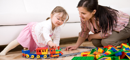 Toddler plays with train on floor