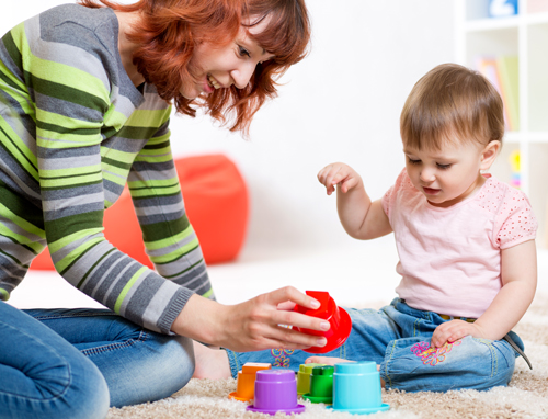 Young mother plays with and teaches her toddler